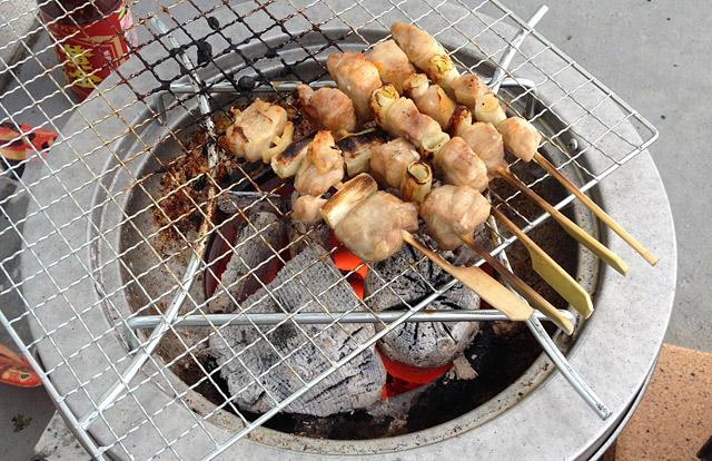焼き鳥串を網と炭火で焼く。