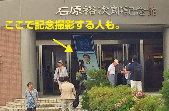 入口のタペストリーで石原裕次郎と記念撮影