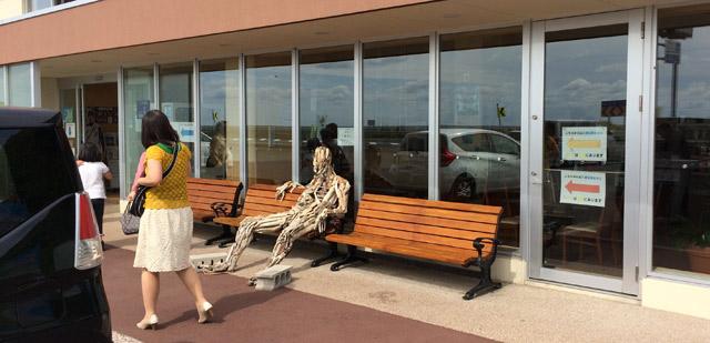 流木の人間がベンチに座るアート